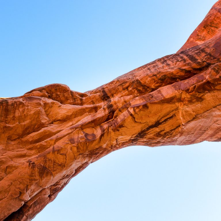 A natural arch spanning across a blue sky in Arches National Park, Utah