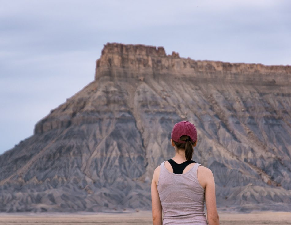 A woman (Olivia Brooks) looking at Factory Butte.